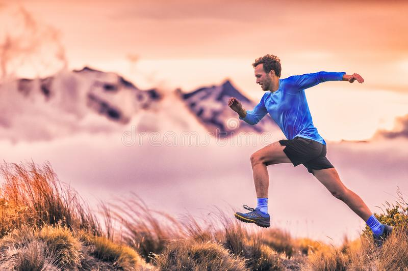 Sport runner trail running man in mountains cold clouds and hills. Male athlete training cardio jumping against altitude sky royalty free stock images