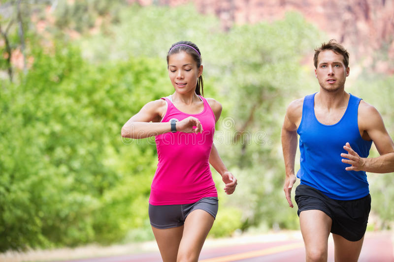 Sport - running fitness mixed couple training. Runners - mixed multicultural couple training outside in nature. Fitness asian young smiling model checking time stock images