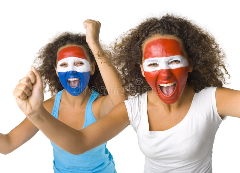 Sport's fans. Young, screaming Austrian and Dutch or Paraguayan sport's fans with painted flags on faces and with clenched fists. Front view. Looking at camera royalty free stock photo