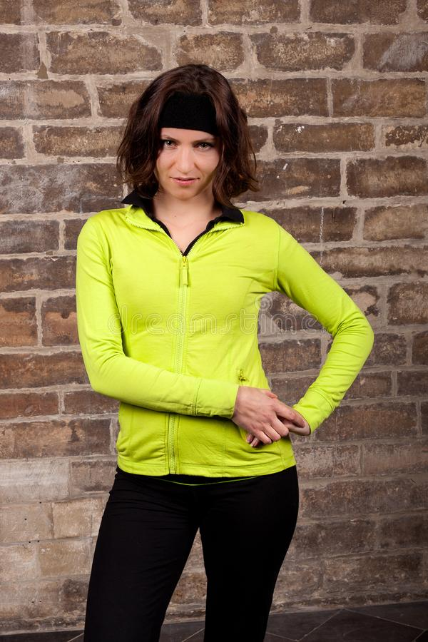 Sport`s woman posing eighties. Slavic sport woman posing is flashy yellow eighties outfit and black panties in front of an antique sand stone wall in the royalty free stock photo