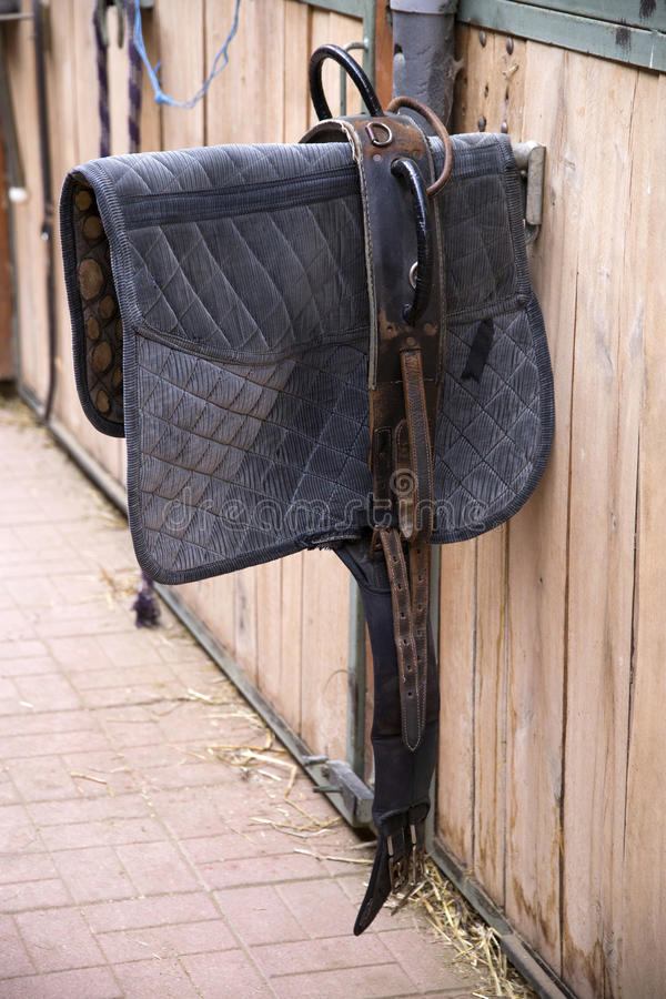 Sport saddle coat for riding trainings. Sporty saddle blanket hanging in a rural barn stock photo