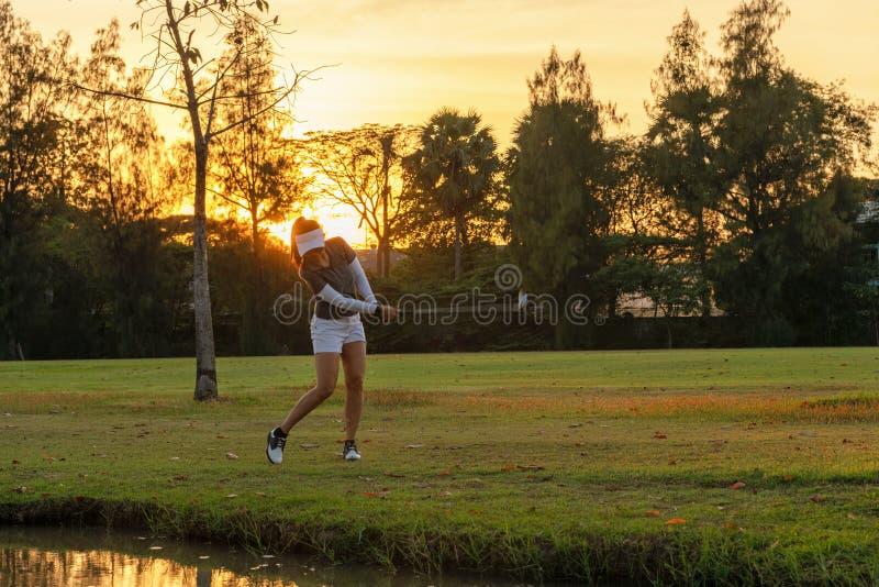 Sport sain Les puces sportives asiatiques de joueur de golfeur de femme et balancer le golf sur le coucher du soleil vert égalisa photographie stock