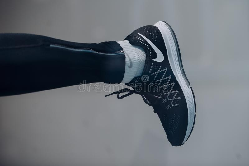 Sport shoe on leg. Running shoe with sock on sole. Trainer or sneaker. Sport footwear and fashion for active lifestyle royalty free stock images