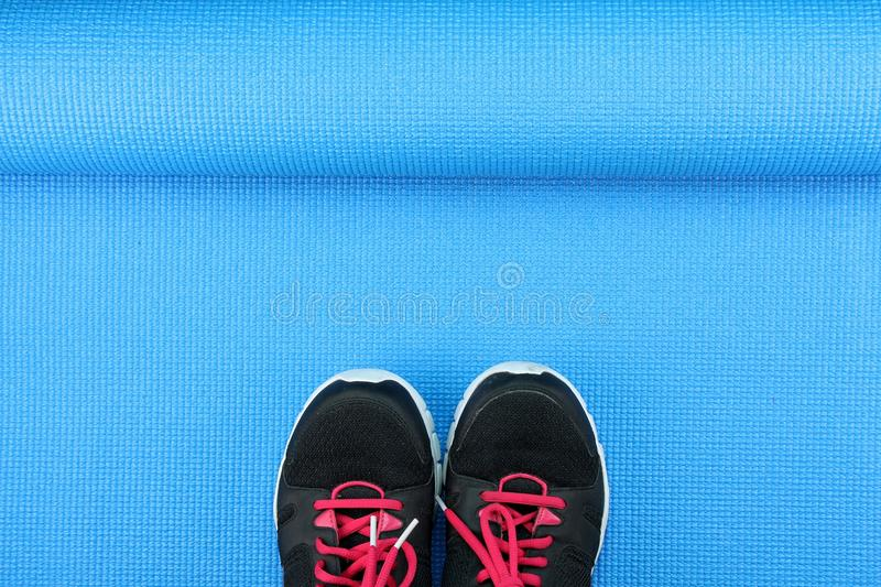 Sport shoes on blue yoga mat background, Fitness accessories. stock image