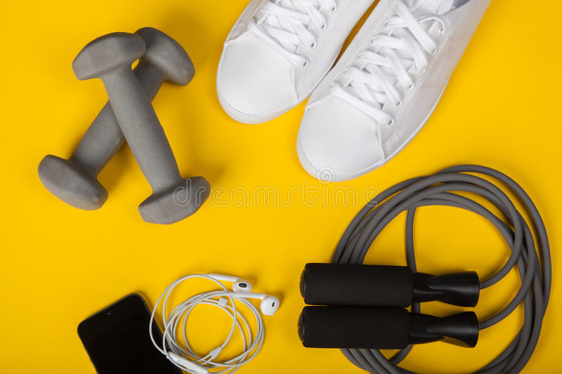 Sport shoes, dumbbells, mobile phone and skipping rope on yellow background. Top view. Fitness, sport and healthy lifestyle concep. Shoes, dumbbells, mobile royalty free stock photos