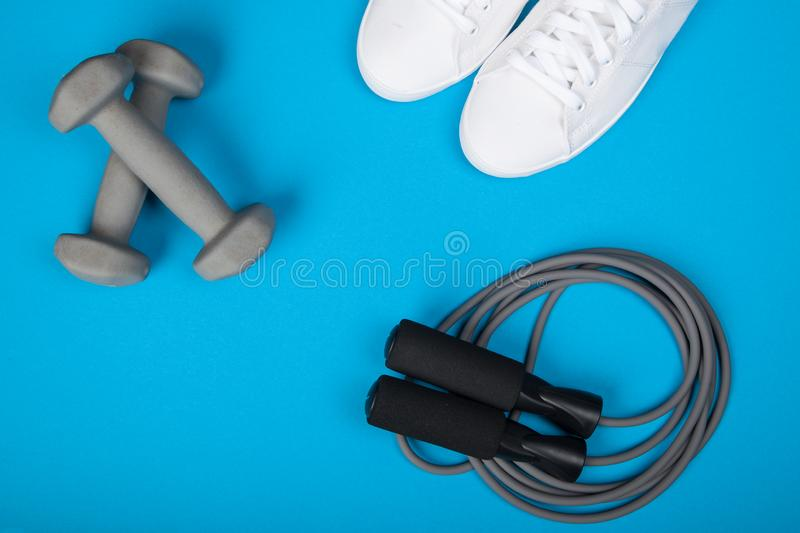 Sport shoes, dumbbells and skipping rope on blue background. Top view. Fitness, sport and healthy lifestyle concept. Sport shoes, dumbbells and skipping rope on stock photos