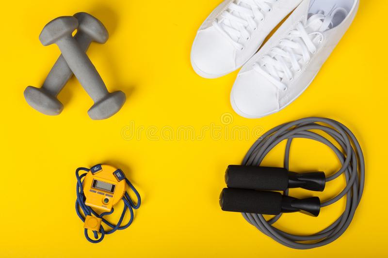Sport shoes, dumbbells, skipping rope and digital stopwatch. Top view. Fitness, sport and healthy lifestyle concept. Sport shoes, dumbbells, skipping rope and royalty free stock photo
