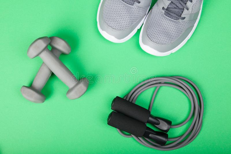 Sport shoes, dumbbells and skipping rope on green background. Top view. Fitness, sport and healthy lifestyle concept. Sport shoes, dumbbells and skipping rope stock images