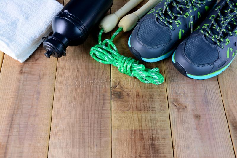 Sport shoes and towel, skipping rope, bottle of water on wooden. Sport shoes and towel, skipping rope, bottle of water royalty free stock photo