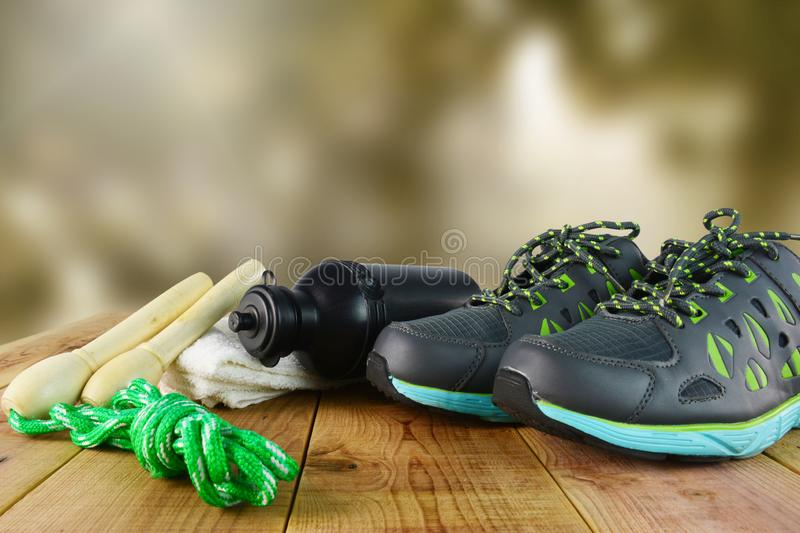 Sport shoes and towel, skipping rope, bottle of water on wooden blur background. Sport shoes and towel, skipping rope, bottle of water stock photos