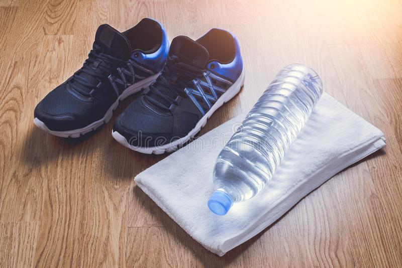 Sport shoes, water, towel on wooden background. In Gym, Fitness royalty free stock photography