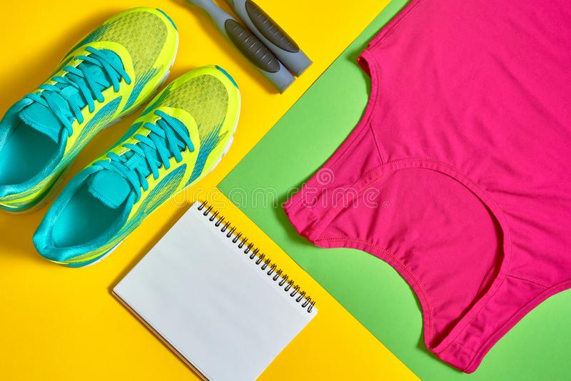 Sport shoes, woman's top bra, white blank notebook and skipping rope on colorful yellow and green backgroundon, copy space. View, flat lay. Sport and royalty free stock photo