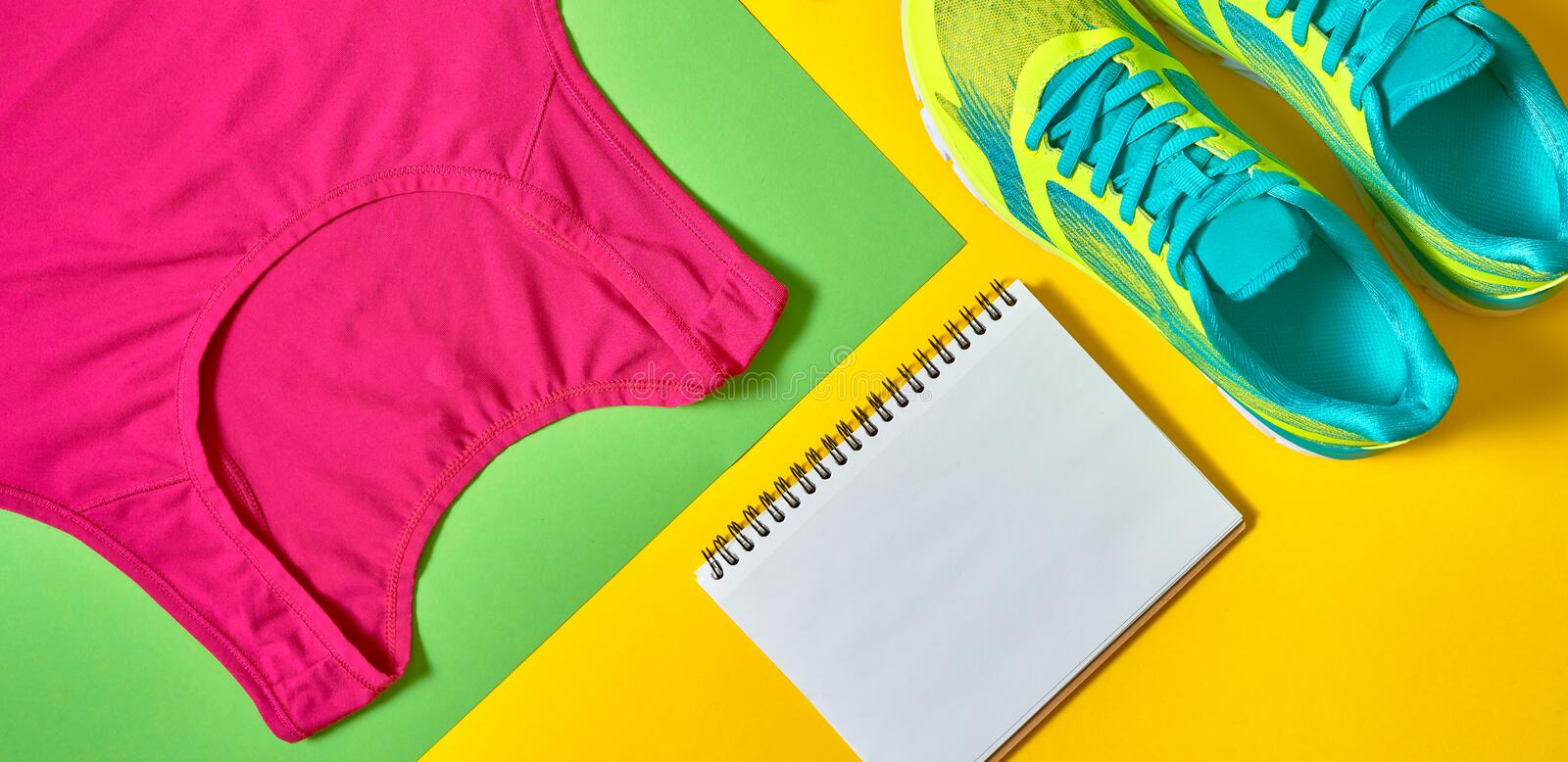 Sport shoes, woman's top bra, white blank notebook and skipping rope on colorful yellow and green backgroundon, copy space. View, flat lay. Sport and stock image