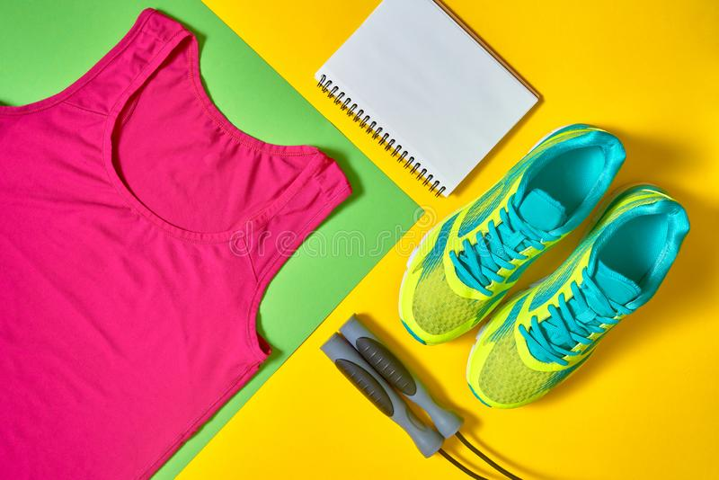 Sport shoes, woman's top bra, white blank notebook and skipping rope on colorful yellow and green backgroundon, copy space. View, flat lay. Sport and stock photos