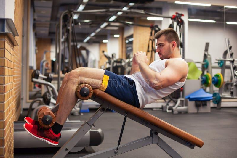 Sport, sprawność fizyczna, bodybuilding, styl życia i ludzie pojęć, - młodego człowieka robić siedzi brzusznego ćwiczenie ławki s zdjęcie royalty free