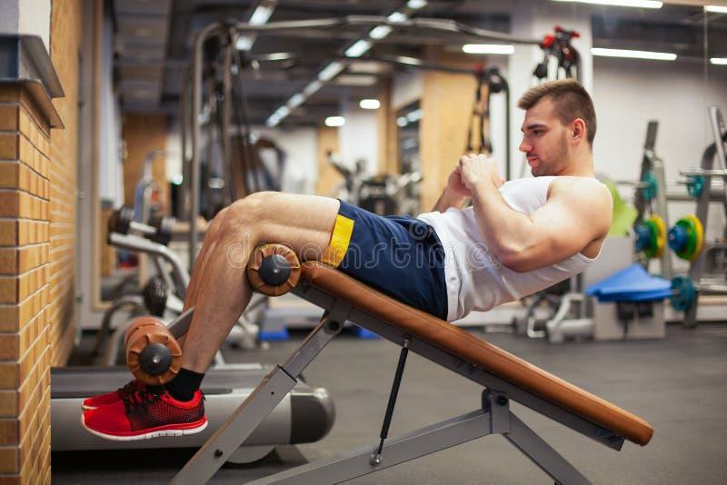Sport, sprawność fizyczna, bodybuilding, styl życia i ludzie pojęć, - młodego człowieka robić siedzi brzusznego ćwiczenie ławki s obraz stock