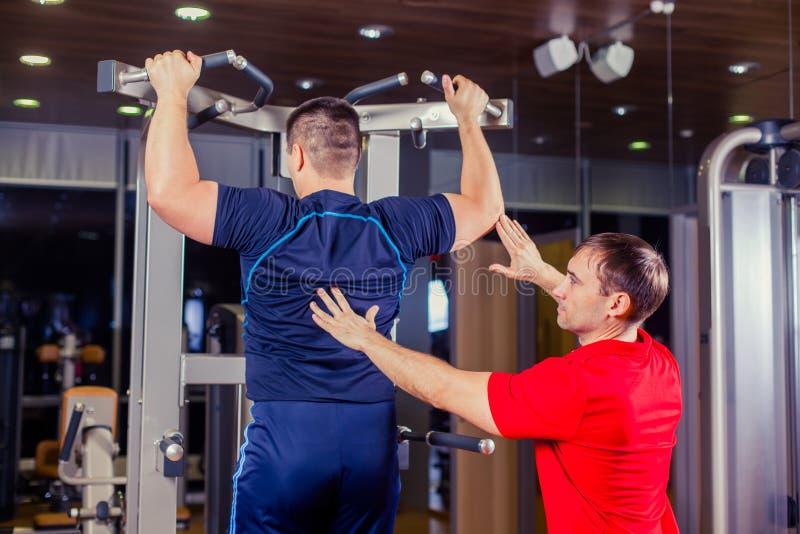 Sport, sprawność fizyczna, praca zespołowa, bodybuilding ludzie pojęć i ogłoszenie towarzyskie trener z barbell ciężaru udźwigu g obrazy royalty free