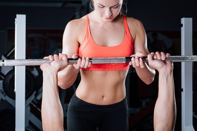 Sport, sprawność fizyczna, praca zespołowa, weightlifting i ludzie pojęć, - młoda dziewczyna trenera osobista praca z mężczyzna b zdjęcia stock