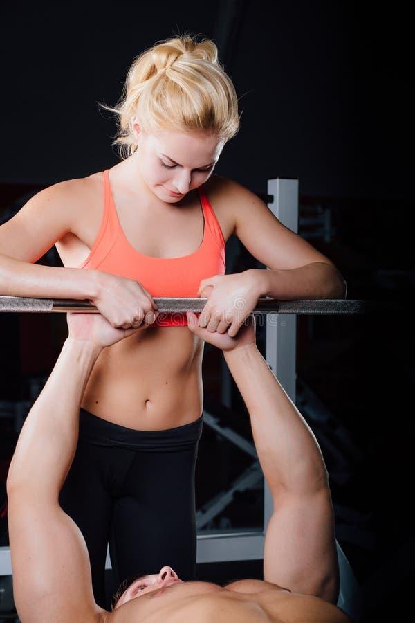 Sport, sprawność fizyczna, praca zespołowa, weightlifting i ludzie pojęć, - młoda dziewczyna trenera osobista praca z mężczyzna b obraz stock
