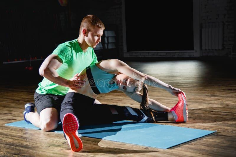 Sport, sprawność fizyczna, styl życia i ludzie pojęć, - uśmiechnięta kobieta z męskim osobistym trenerem ćwiczy w gym stretching zdjęcie royalty free