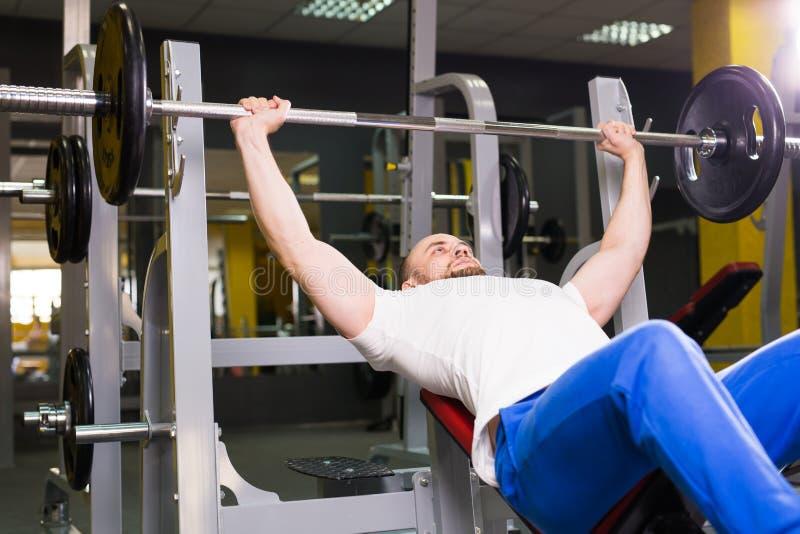 Sport, sprawność fizyczna, szkolenie i ludzie pojęć, - mężczyzna podczas ławki prasy ćwiczenia w gym obrazy royalty free