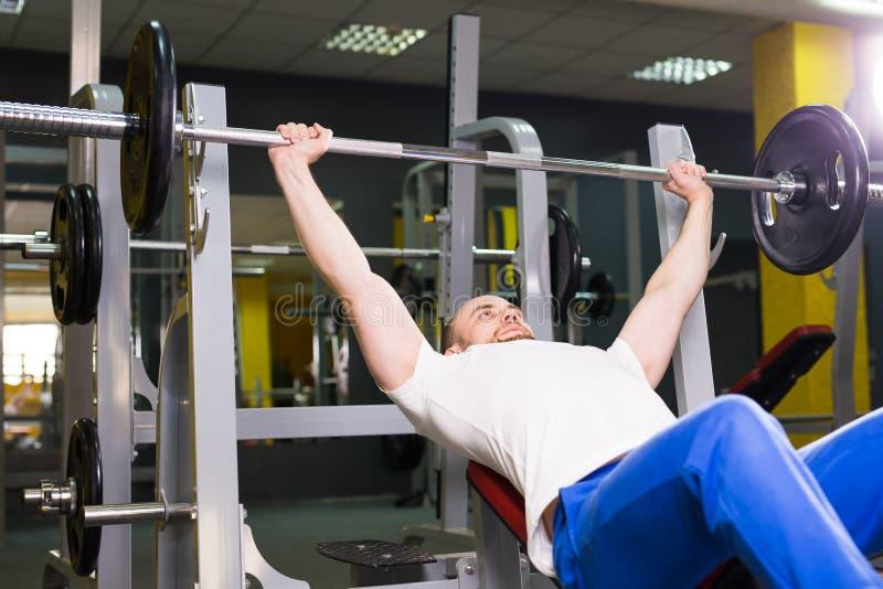 Sport, sprawność fizyczna, szkolenie i ludzie pojęć, - Mięśniowy mężczyzna robi ciężkiemu ćwiczeniu pompuje up mięśnie na ławki p zdjęcie stock