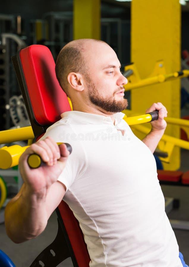 Sport, sprawność fizyczna, szkolenie i ludzie pojęć, - Mięśniowy mężczyzna robi ciężkiemu ćwiczeniu pompuje up mięśnie w gym obrazy stock