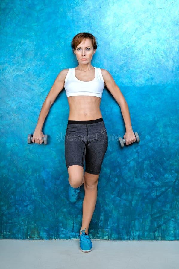 Sport sprawności fizycznej dziewczyna blisko błękitnej ściany zdjęcie stock