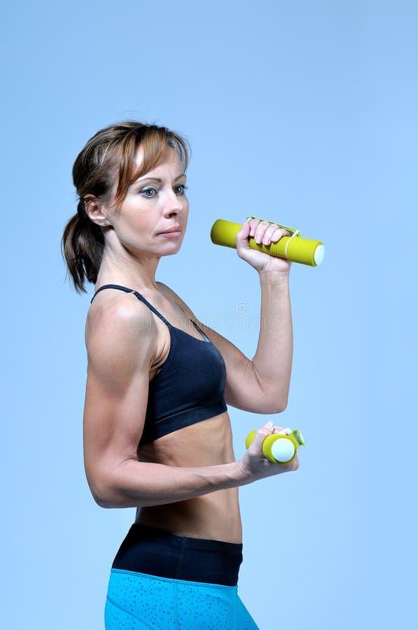 Sport sprawności fizycznej kobieta robi ćwiczeniu z żółtym dumbbell obraz stock