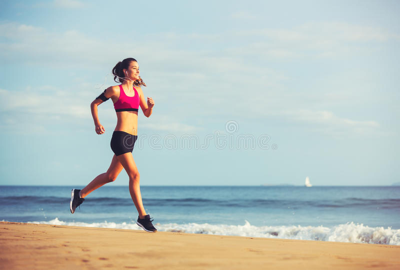 Sport sprawności fizycznej kobiety bieg na plaży przy zmierzchem zdjęcia stock