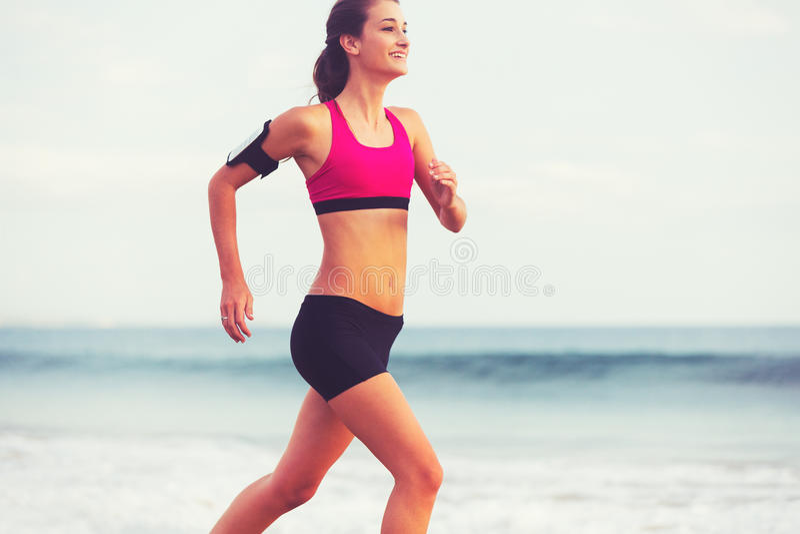 Sport sprawności fizycznej kobiety bieg na plaży przy zmierzchem obraz stock