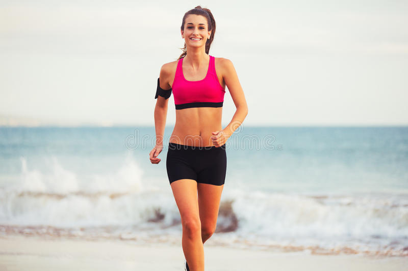 Sport sprawności fizycznej kobiety bieg na plaży przy zmierzchem zdjęcia royalty free