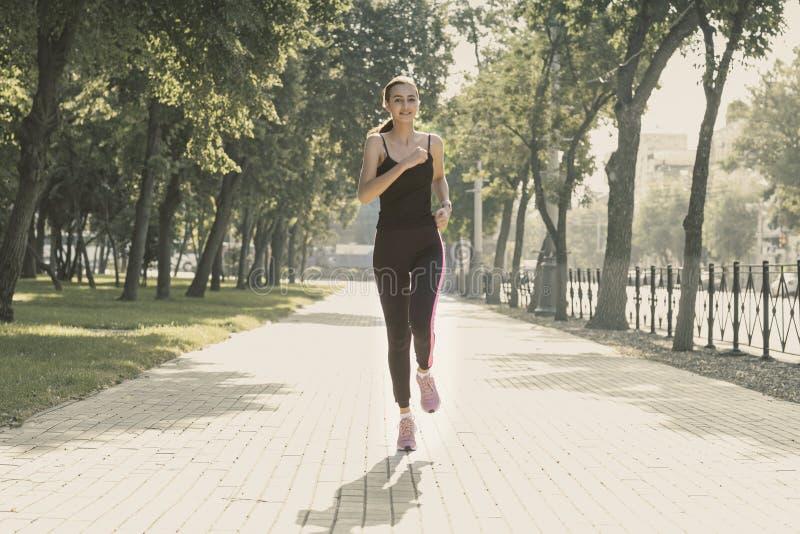 Sport sprawności fizycznej kobiety bieg w miasteczko parku na letnim dniu poj?cie odizolowywaj?cy sporta biel zdjęcia royalty free