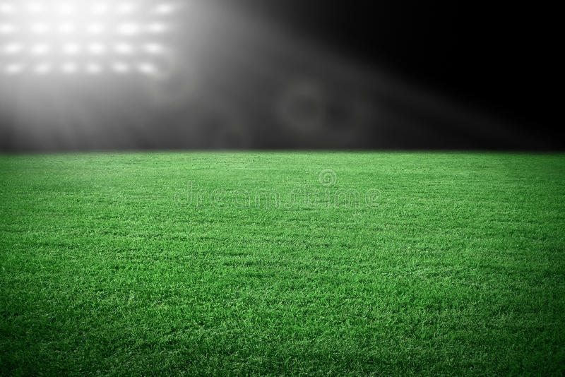 Sport stadium. In the spotlight with green grass field royalty free stock photography