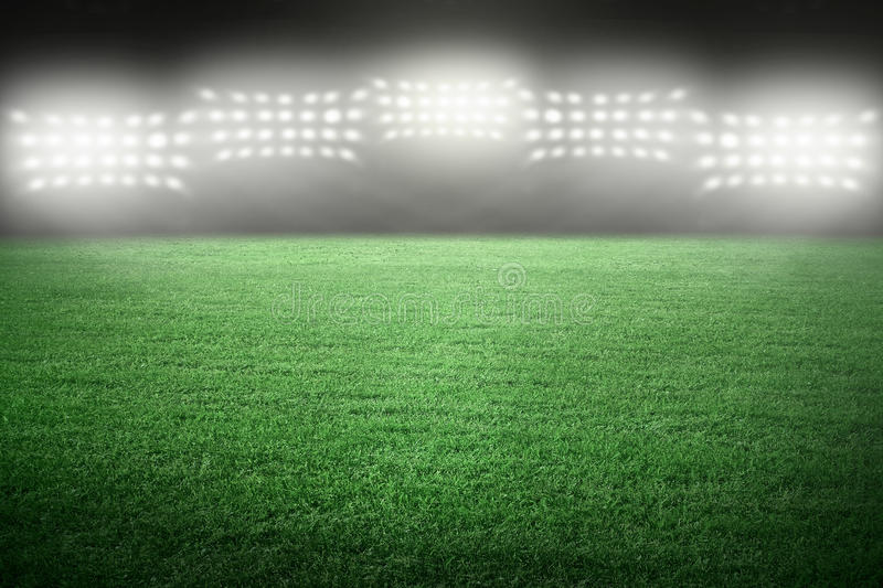 Sport stadium. In spotlight with green grass field royalty free stock photo