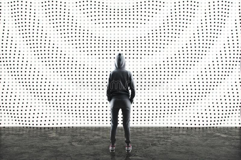 Sport style woman looking at abstract LED display. On the wall in a space with concrete floor stock photo