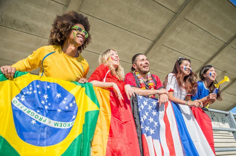 Sport supporters at stadium. Group of sport supporters at stadium - Fans of diverse nations screaming to support their teams - Multi-ethnic people having fun and stock image