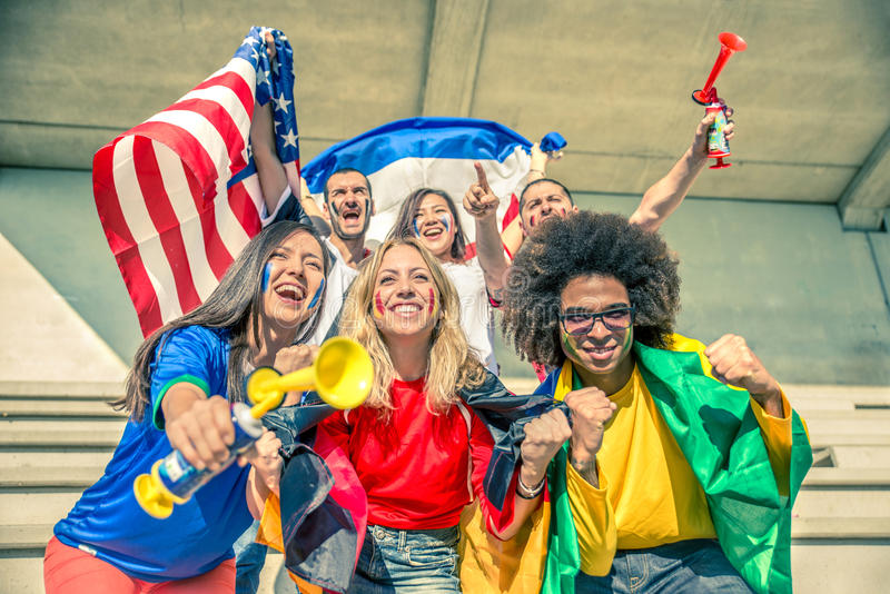 Sport supporters at stadium. Group of sport supporters at stadium - Fans of diverse nations screaming to support their teams - Multi-ethnic peoplehaving fun and stock photo