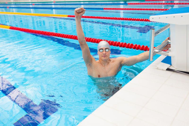 Sport swimmer winning. Man swimming cheering celebrating victory success smiling happy in pool wearing swim goggles and royalty free stock images