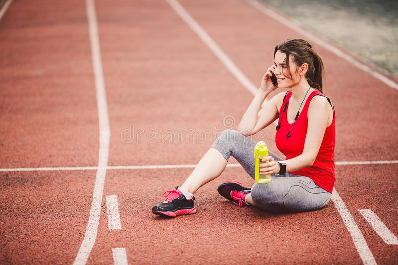 Sport and technology. A beautiful young Caucasian woman with ponytail sitting resting after workout during run at stadium, a red t royalty free stock images