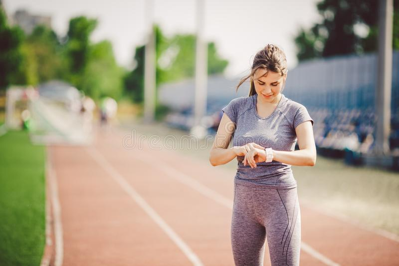 Sport and technology. beautiful young whiteskinned woman with ponytail at running stadium in front of workout uses a sporty smart. Clock on her arm to control stock photo