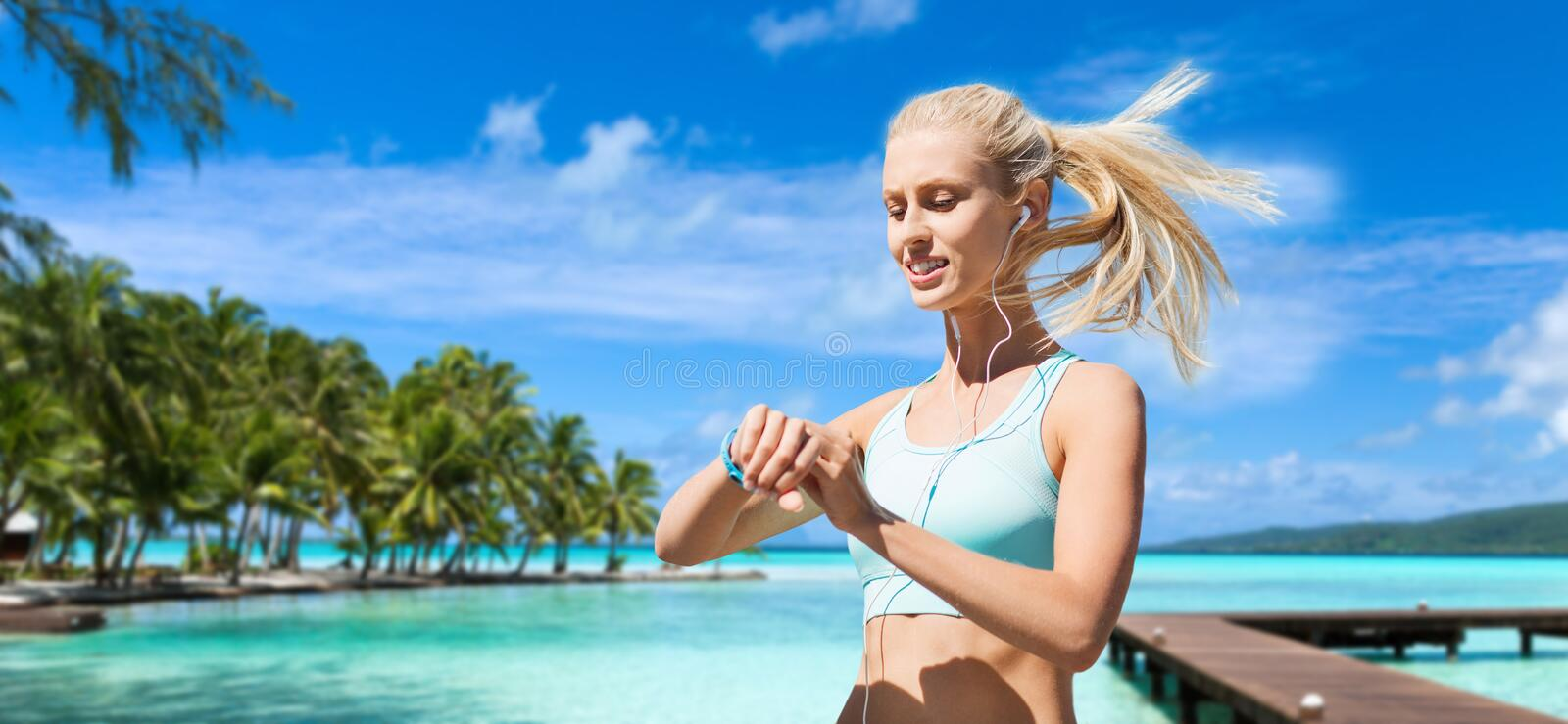 Happy woman with fitness tracker and earphones stock photography