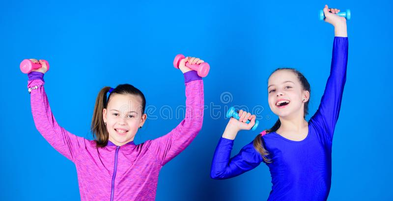 Sport for teens. Easy exercises with dumbbell. Sporty upbringing. On way to stronger body. Girls exercising with. Dumbbells. Beginner dumbbells exercises stock images