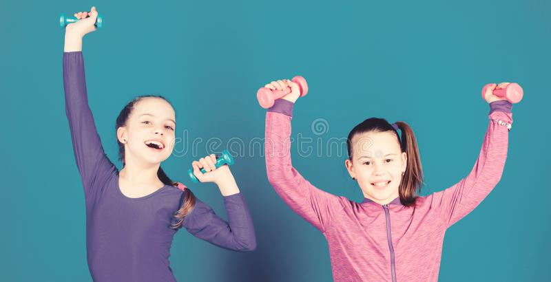 Sport for teens. Easy exercises with dumbbell. Sporty upbringing. On way to stronger body. Girls exercising with. Dumbbells. Beginner dumbbells exercises royalty free stock photo