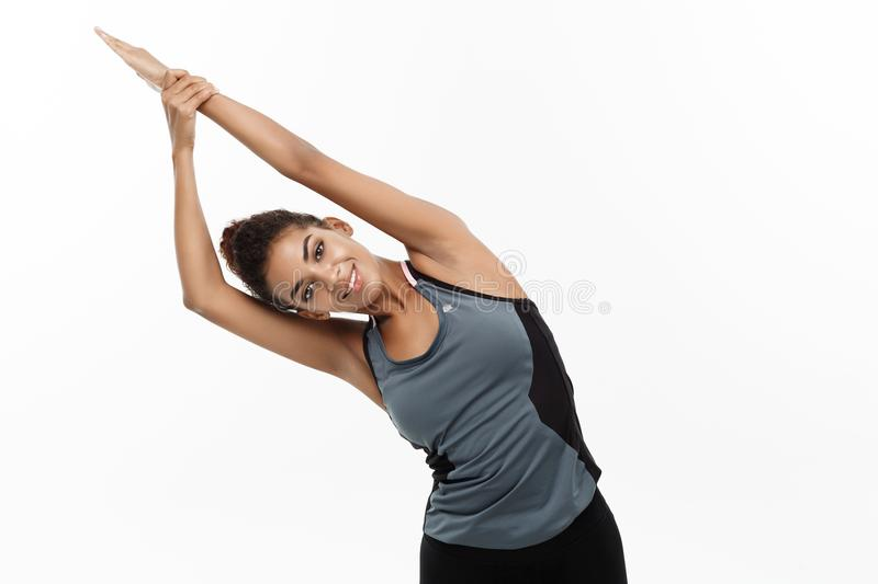 Sport, training, lifestyle and Fitness concept - portrait of beautiful happy African American woman stretching hands stock photography