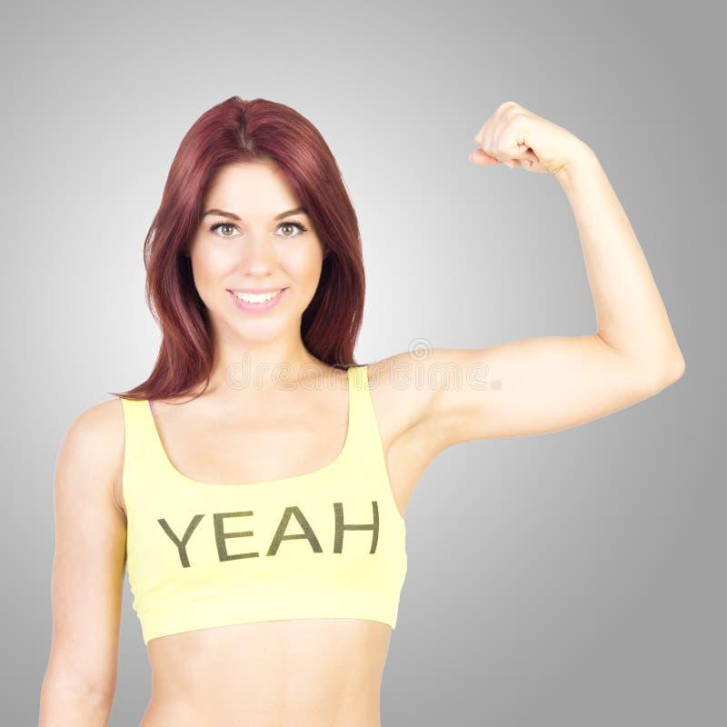 Sport uśmiechnięta kobieta pokazuje daleko jego mięśnie na szarym tle Sporty i sprawność fizyczna obraz royalty free