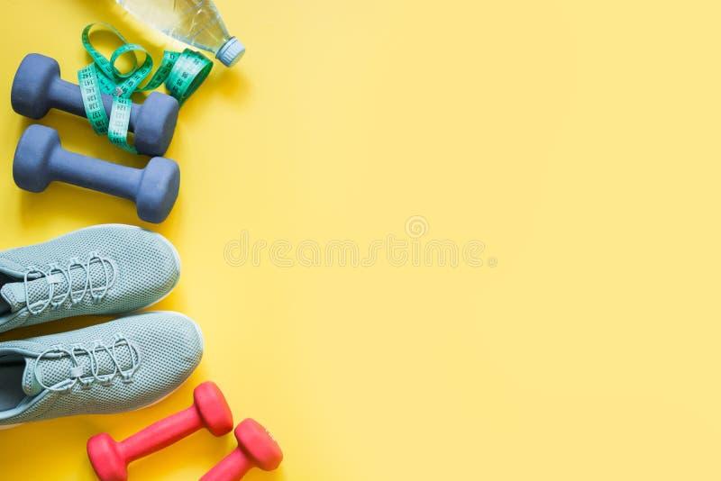Sport- und Eignungsausr?stung, Dummk?pfe, Eignungsschuhe, messendes Band auf schlagkr?ftigem Gelb Draufsicht, Raum f?r Text lizenzfreies stockbild