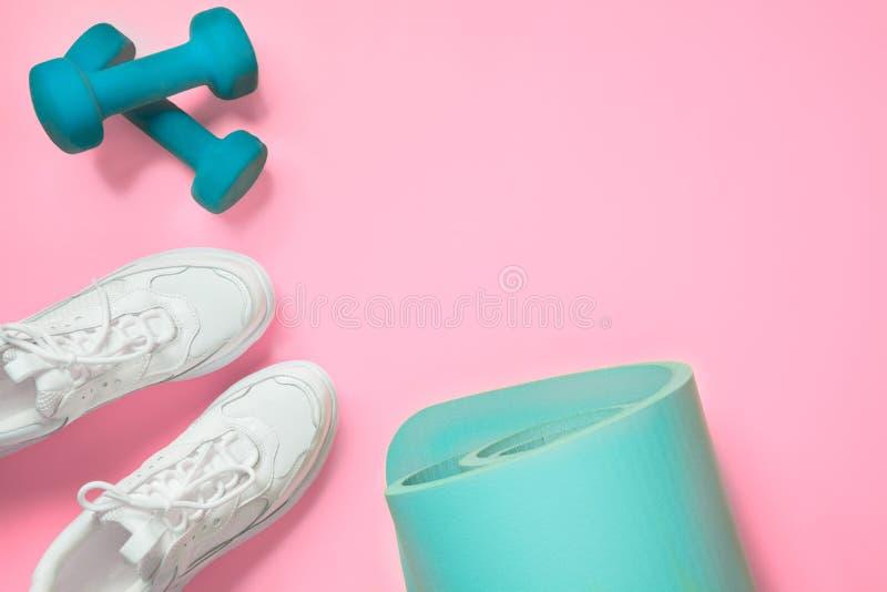 Sport- und Fitnessschuhe, Dumbell, Yogamat auf Rosa Textbereich stockfotografie