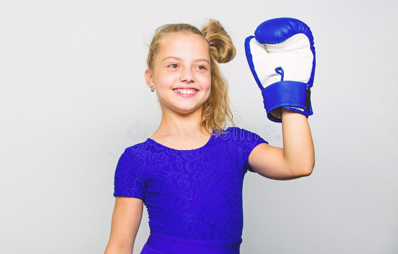 Sport upbringing for girls. Feminist movement. Strong child concept. Kid strong and healthy. Girl child strong with. Boxing gloves posing on grey background stock photography