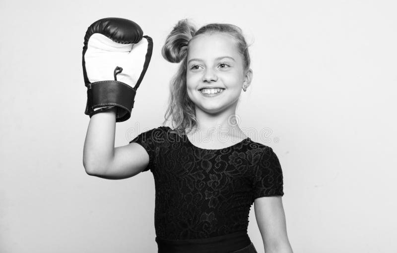 Sport upbringing for girls. Feminist movement. Strong child concept. Kid strong and healthy. Girl child strong with. Boxing gloves posing on grey background royalty free stock photography